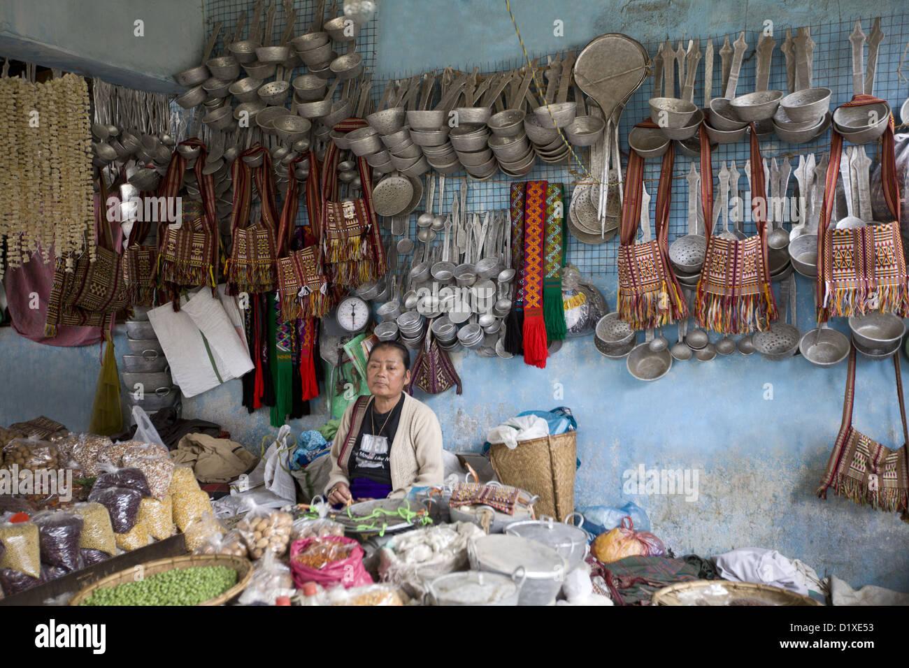 Lady selling vegetables and utensils. Bomdila bazaar, Arunachal Pradesh, India. - Stock Image