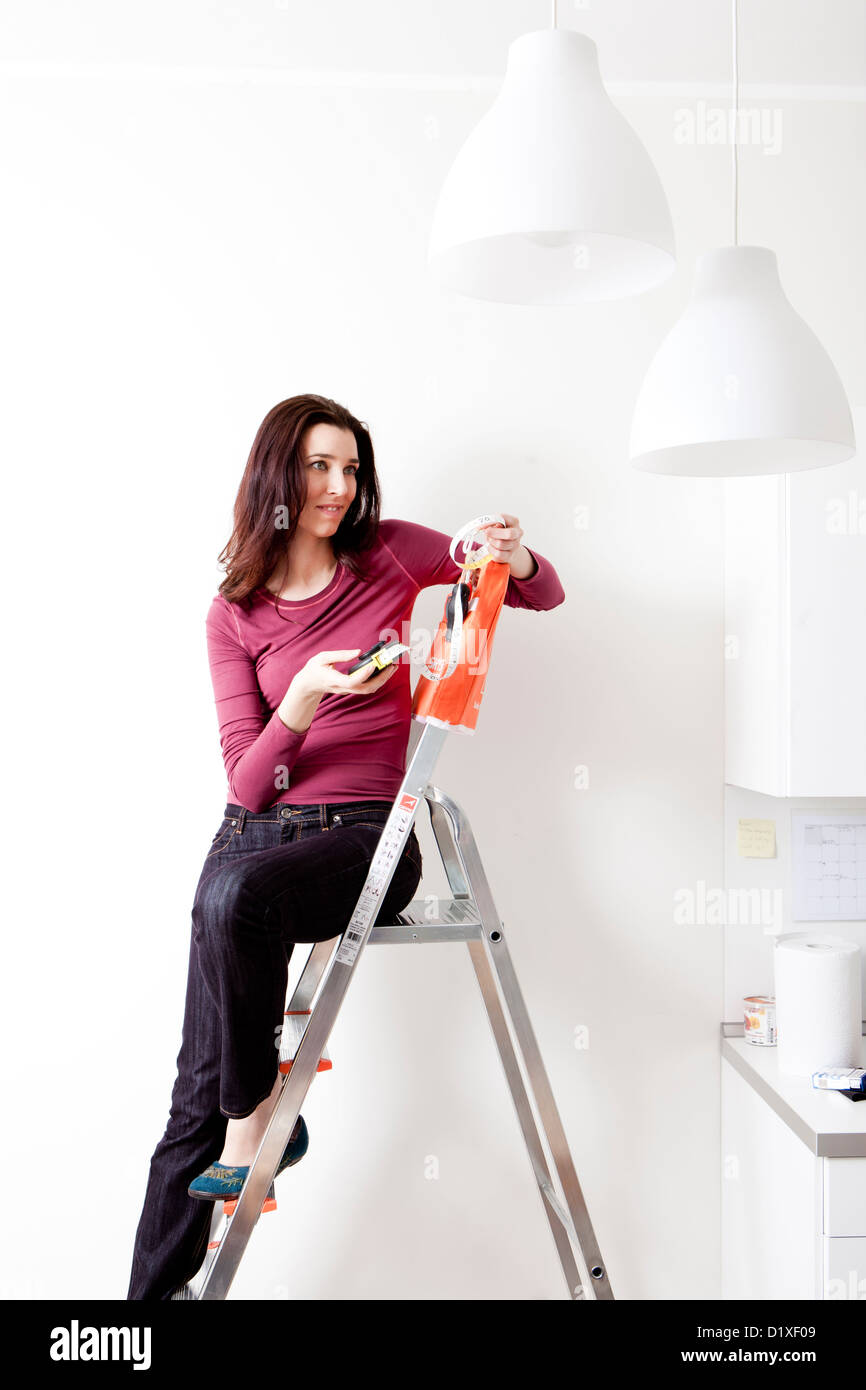 woman with meter measures the walls of the house - Stock Image