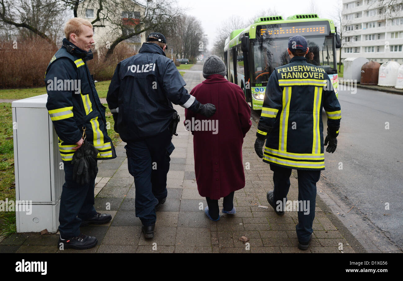 Rescue team accompanies a woman to a bus in Hanover, Germany, 06 January 2013. More than 25,000 people had to be - Stock Image