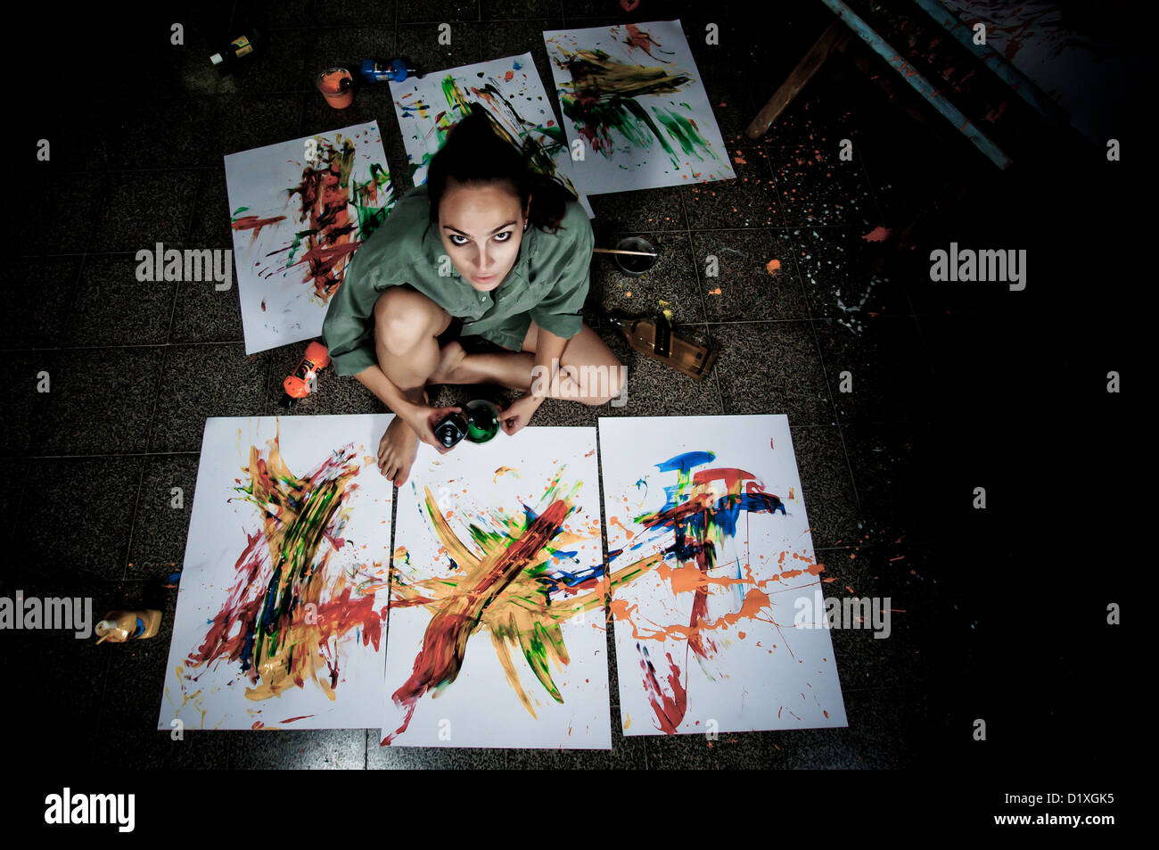 A young female artist painter works in her studio - Stock Image