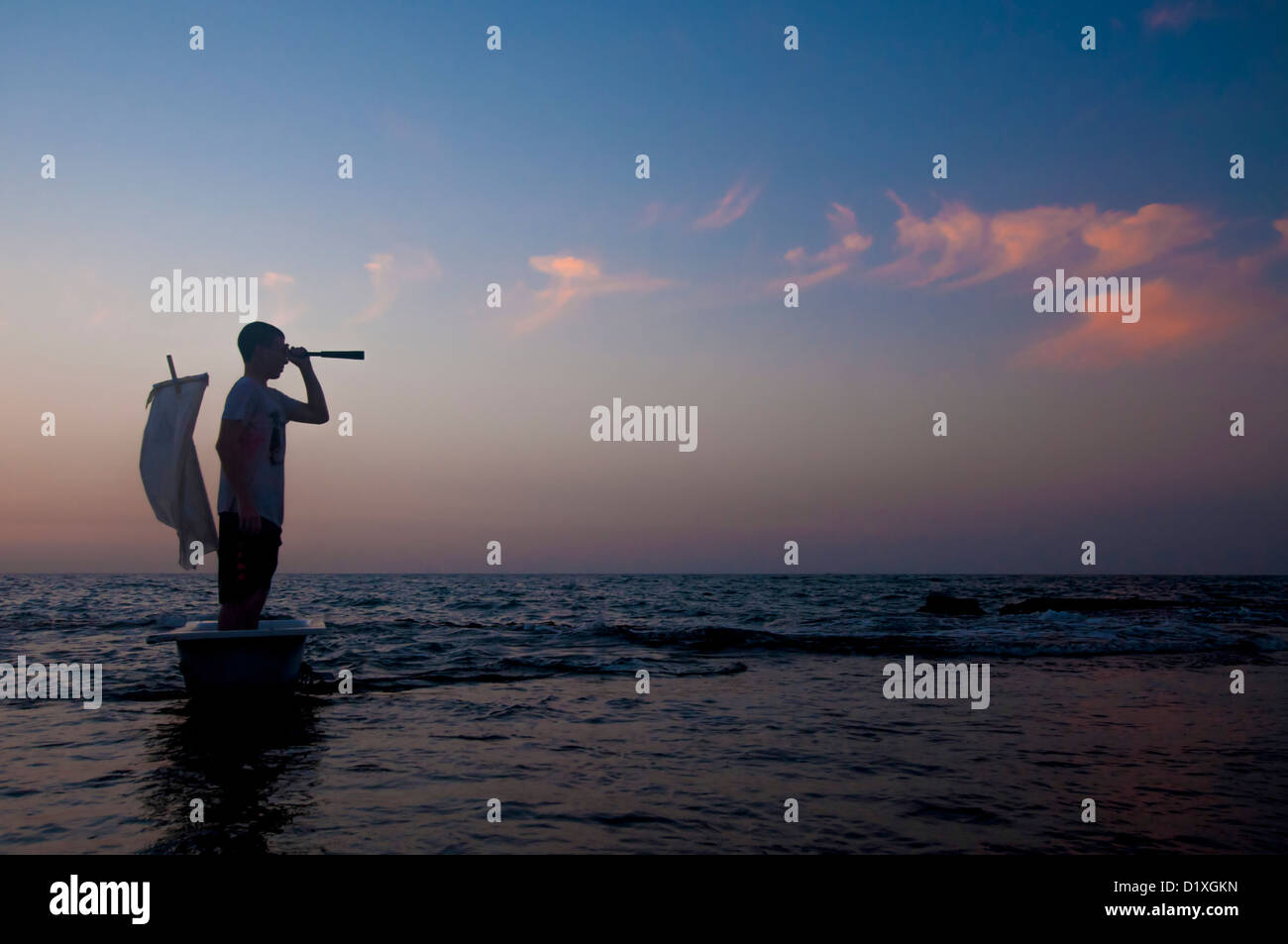 Silhouette of a man standing in a bathtub like boat with a telescope - Stock Image