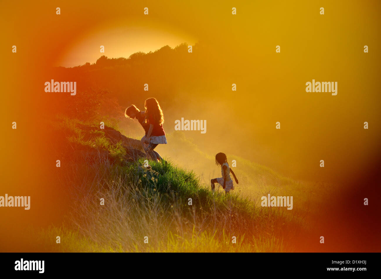 Three girls playing in fields with bright orange glow all around. Mood shot. Western Cape, South Africa - Stock Image