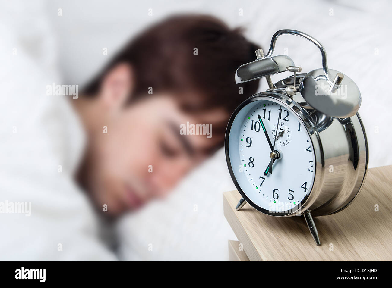 Close up of an old fashioned alarm clock, young man asleep - Stock Image
