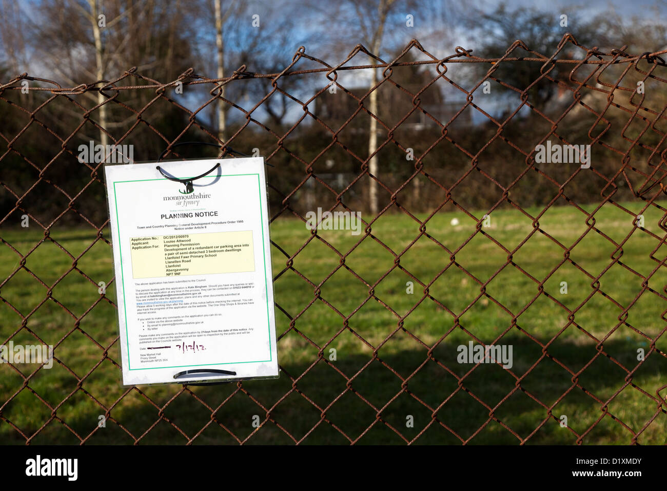 Planning permission notice on fence concerning proposed infill housing building in centre of village, Llanfoist, - Stock Image