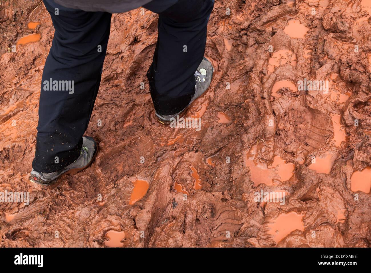 Person walking on very muddy footpath, Skirrid, Wales, UK - Stock Image