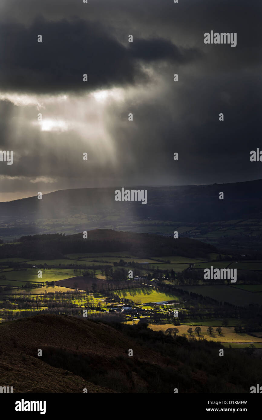 Dark clouds with rays of sunlight over a Welsh valley, Abergavenny, Wales, UK - Stock Image