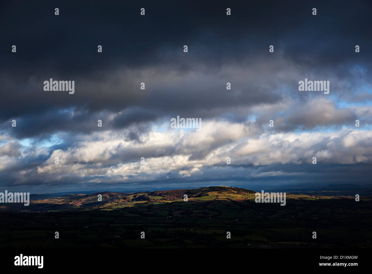 Dark skies over fields and moors lit through a gap in the clouds, from the Skirrid, Wales, UK - Stock Image