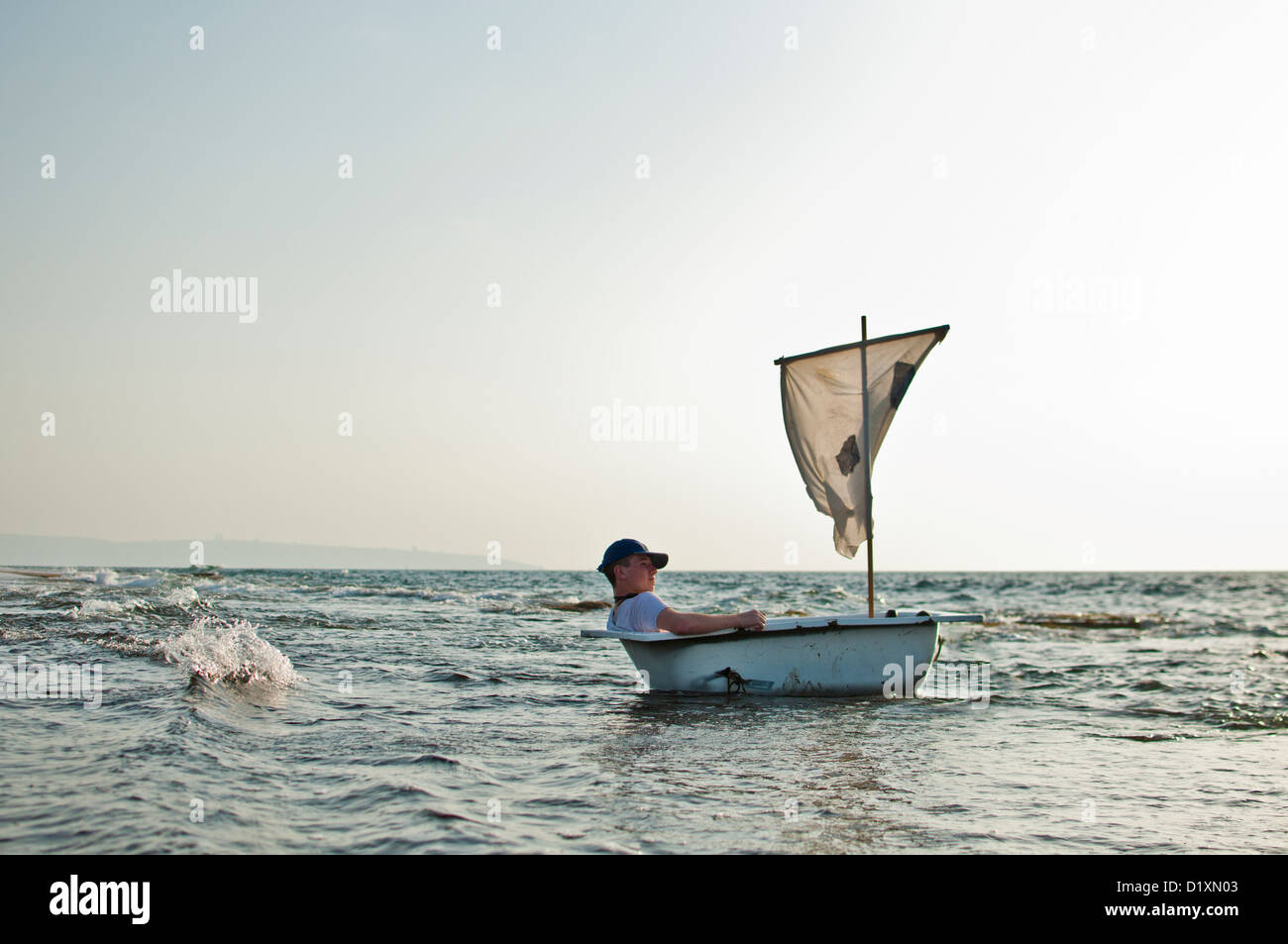 Man In A Bathtub Like Boat With A Sail In The Sea   Stock Image