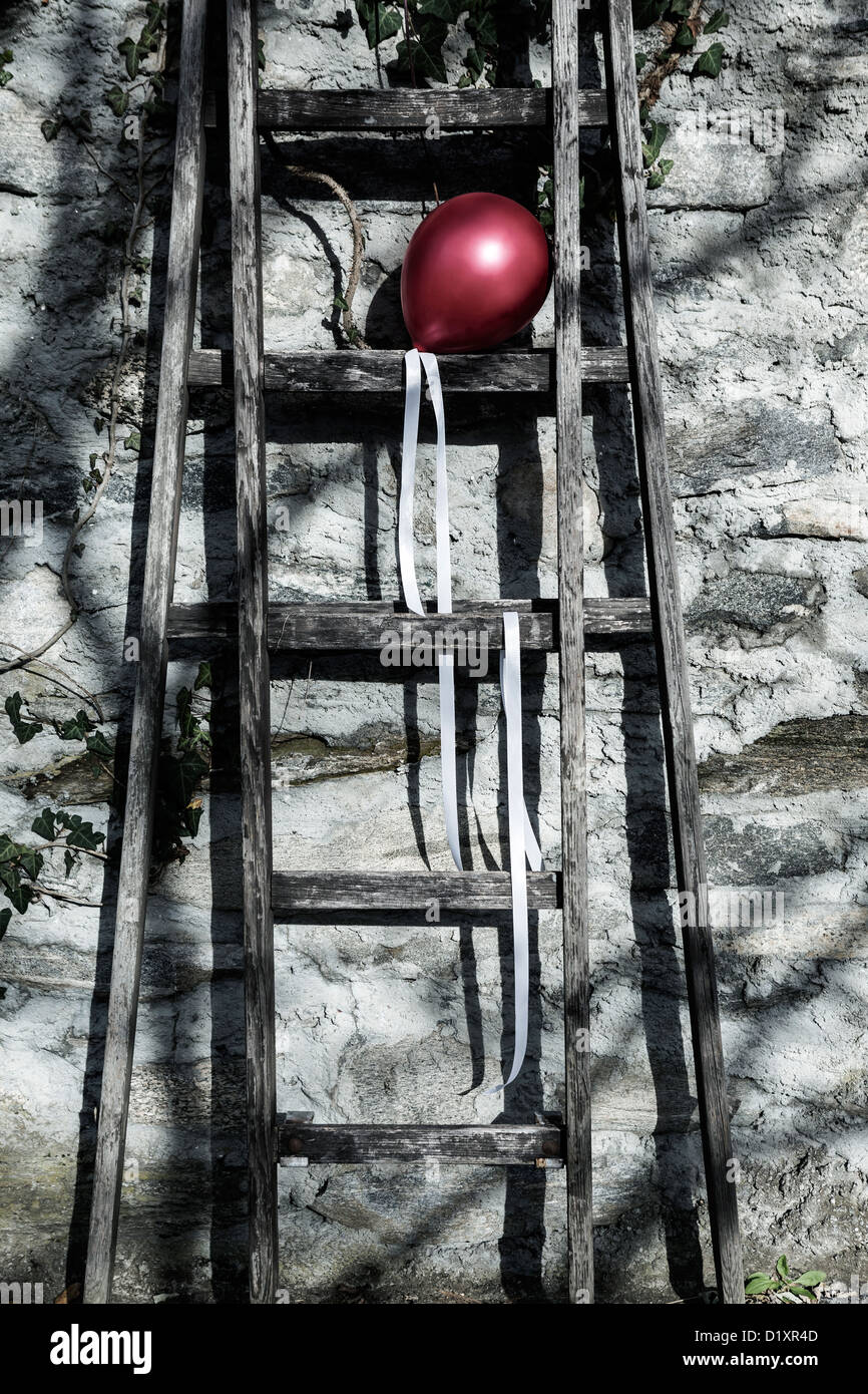 a red balloon on an old wooden ladder - Stock Image