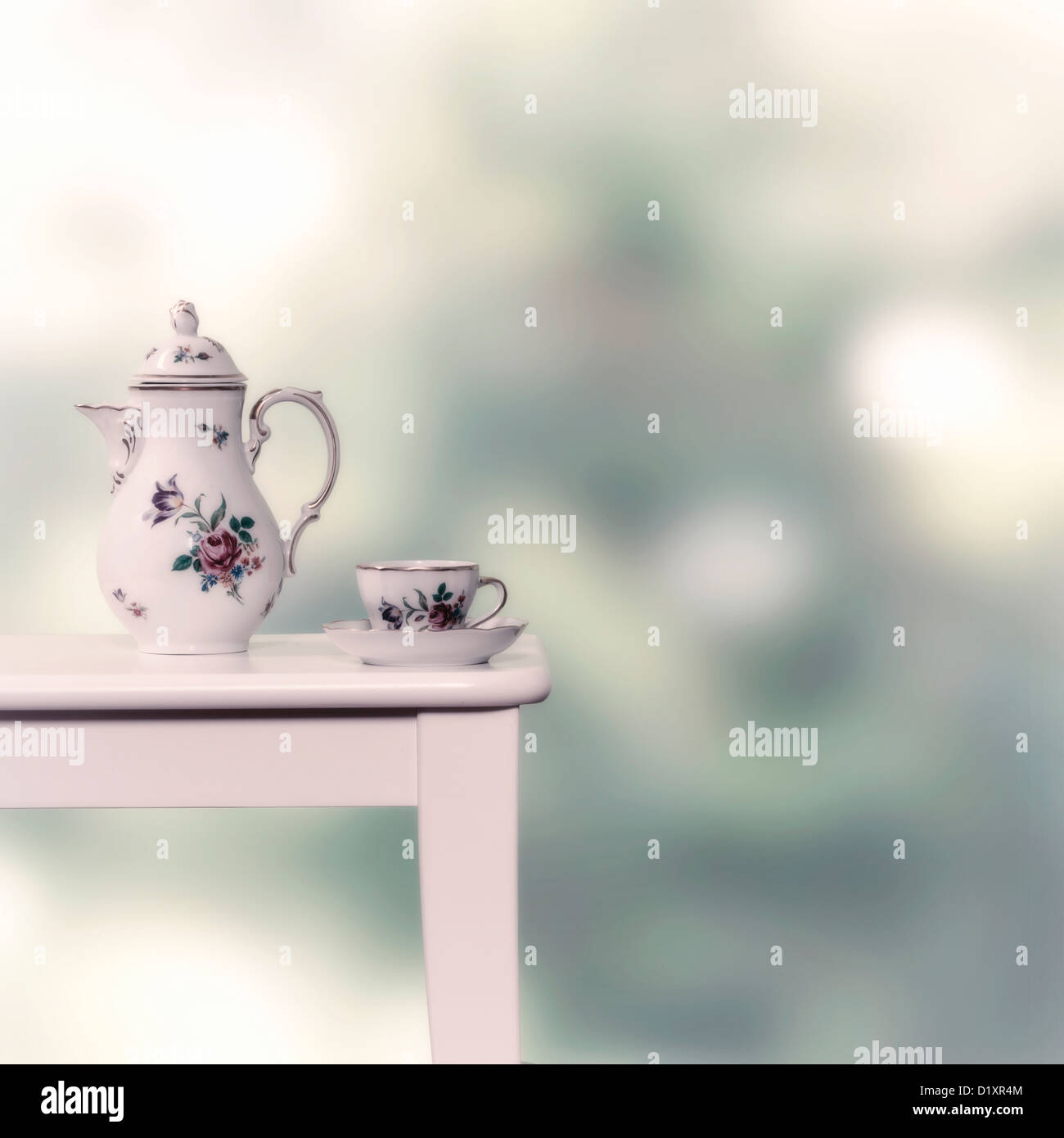 vintage tea pot and cup on a white stool - Stock Image
