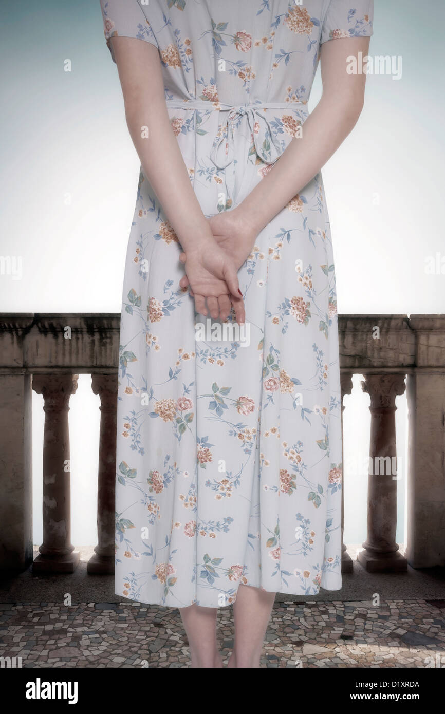 a woman in a vintage floral dress is standing on a balcony - Stock Image