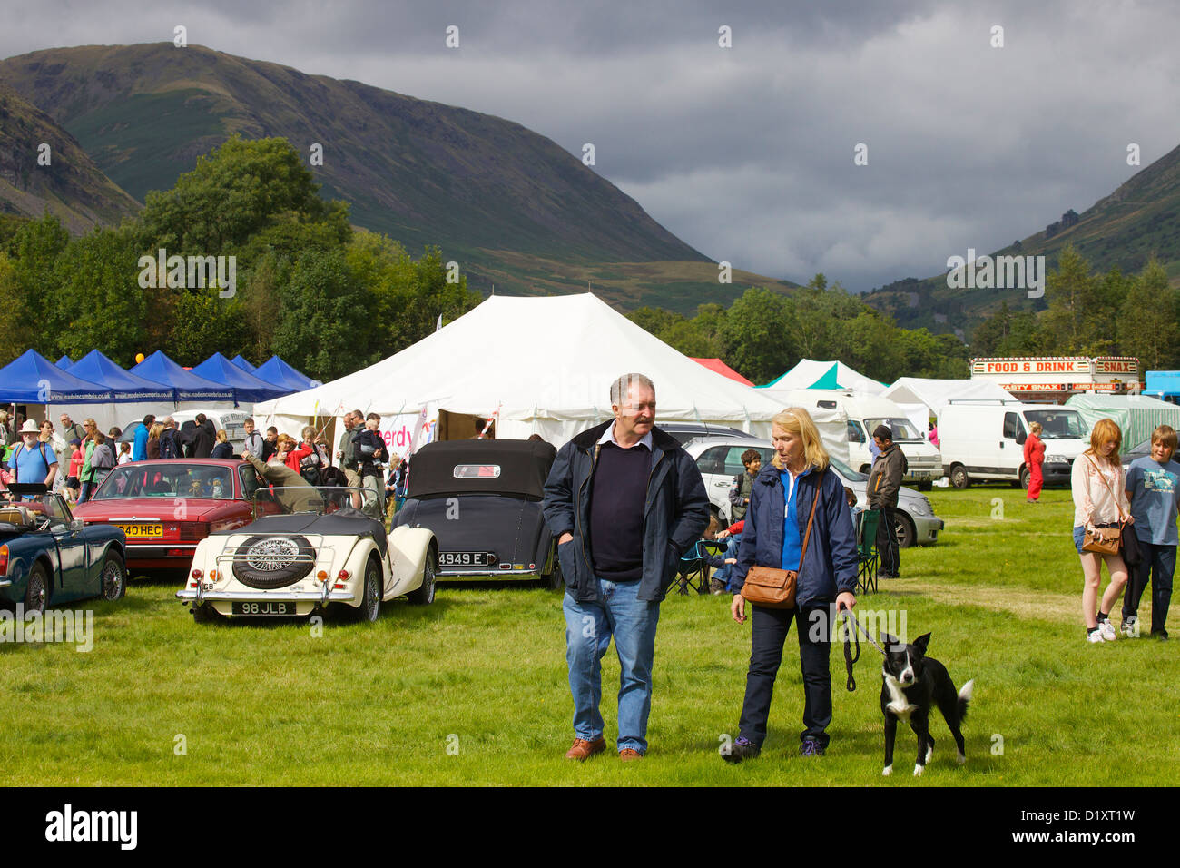 Man and woman walking their dog at Grasmere Lakeland Sports,Lake District National Park,Cumbria, England. United - Stock Image