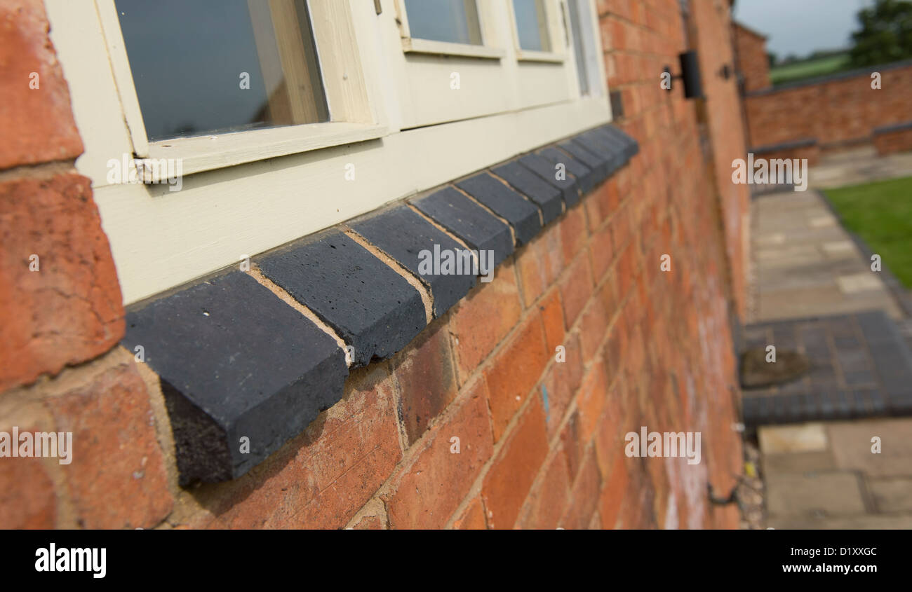 Close up view of a brick sill beneath a window on a newly converted barn in the English countryside. - Stock Image