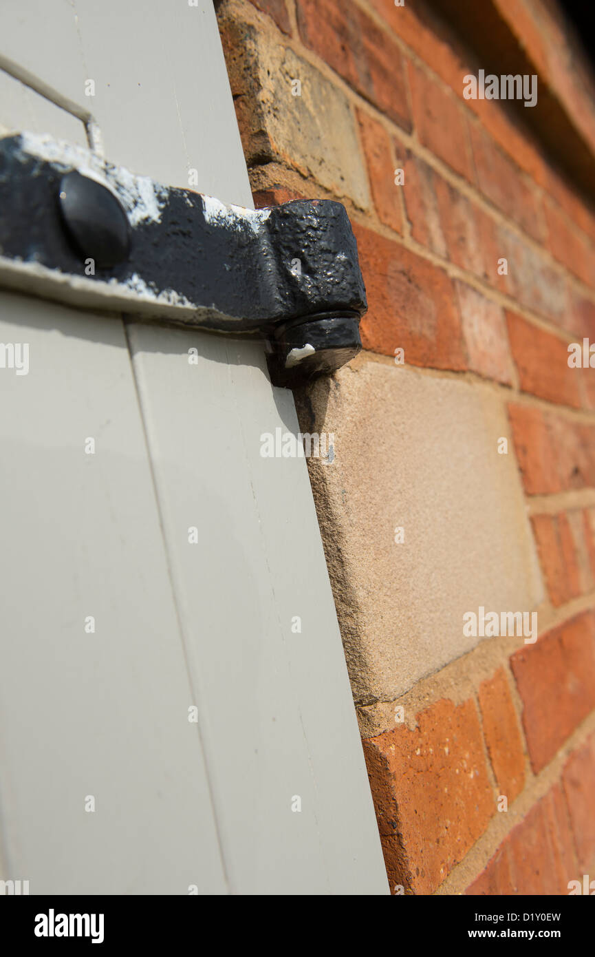 Close up of an iron hinge on a door on a new barn conversion. - Stock Image