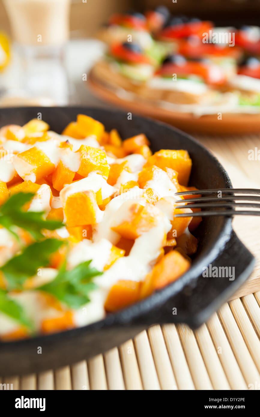 pumpkin baked in sour cream in a pan, close-up - Stock Image