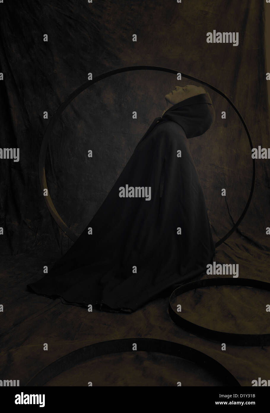 Calm cloaked female figure in circles and darkness. - Stock Image