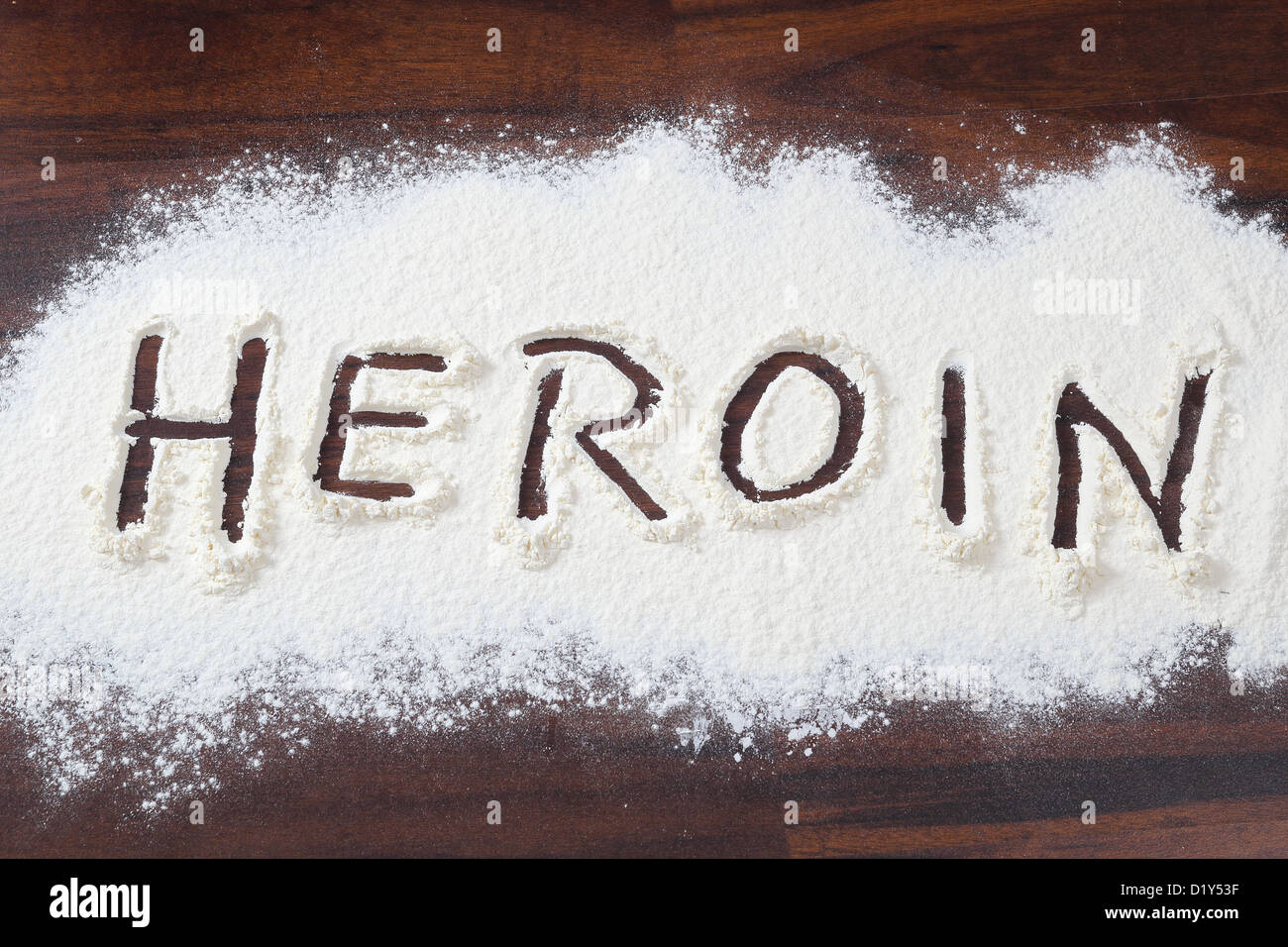 The word heroin written in a white powder - Stock Image