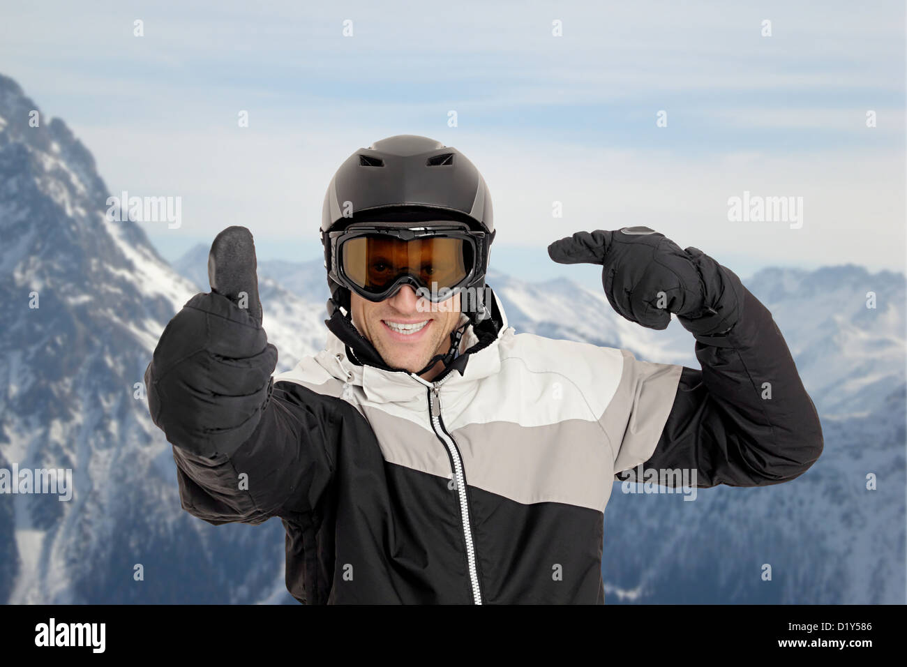 Skier pointing on his helmet in front of mountains - Stock Image