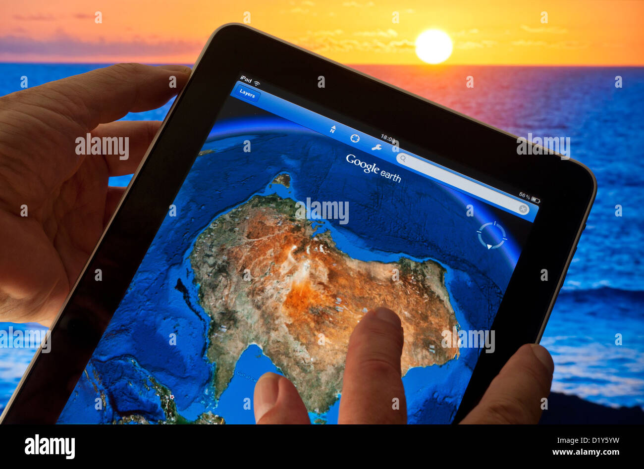 GOOGLE EARTH AUSTRALIA Hands holding Apple iPad with Google Earth application on screen featuring map of Australia - Stock Image