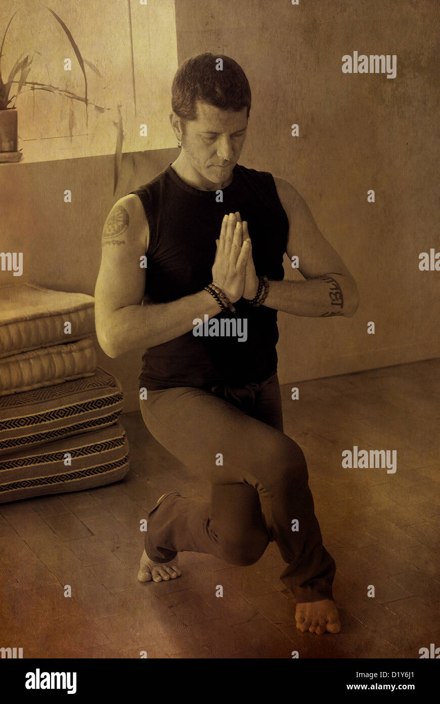Man in a deep eagle leg squat holding his hands in prayer pose. - Stock Image