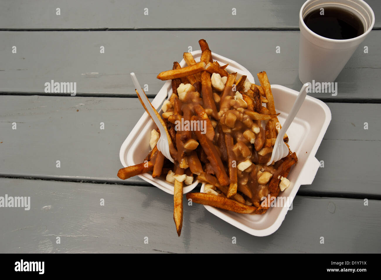 The traditional Canadian dish of poutine (French fried potatoes topped with gravy and cheese curds) served with - Stock Image