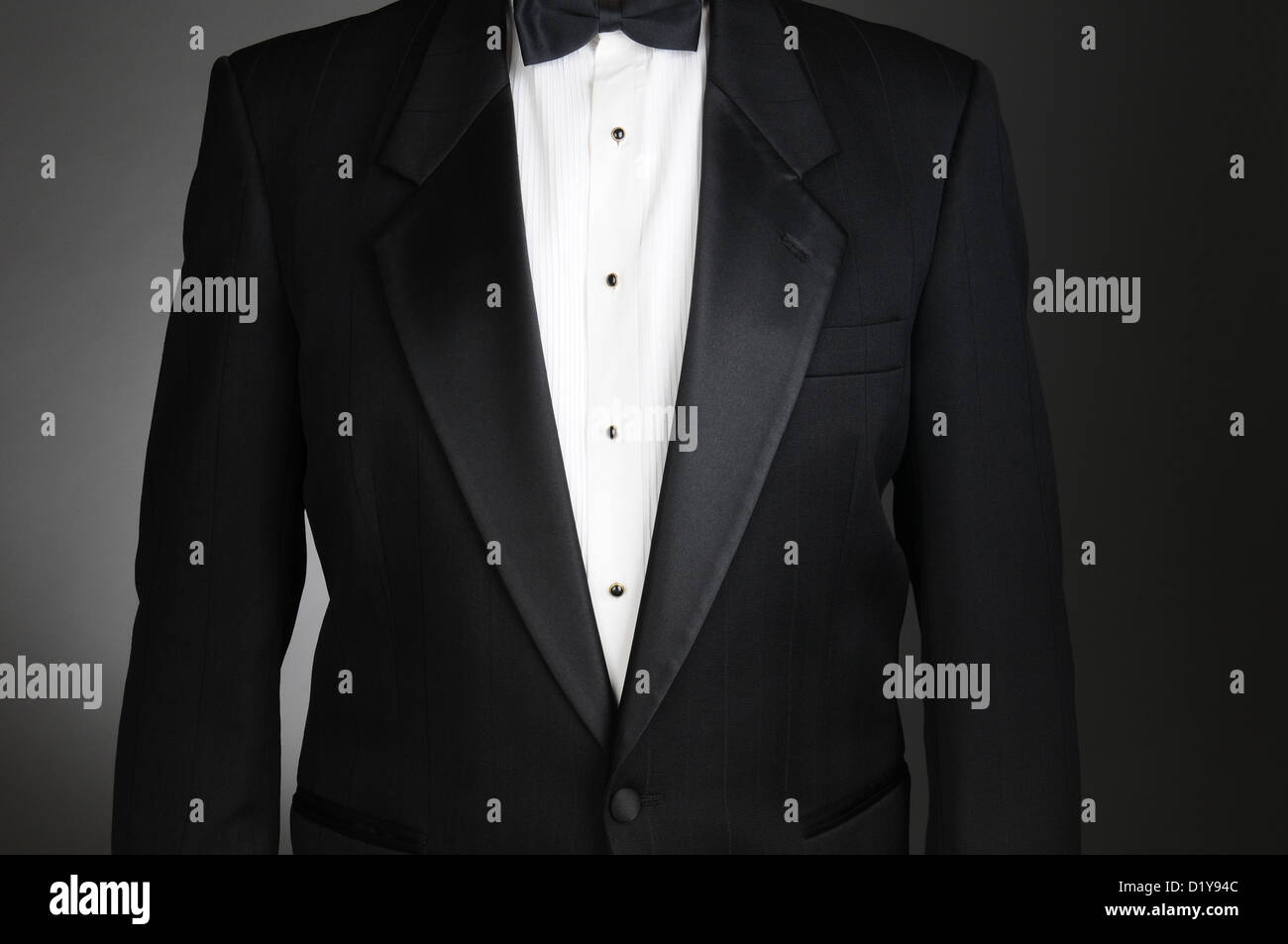 Closeup of a Black Tuxedo Jacket. Torso only on a light to dark gray background. Horizontal format. - Stock Image
