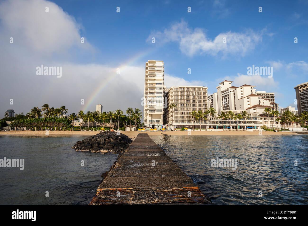 Rainbow above Waikiki high rise towers. - Stock Image