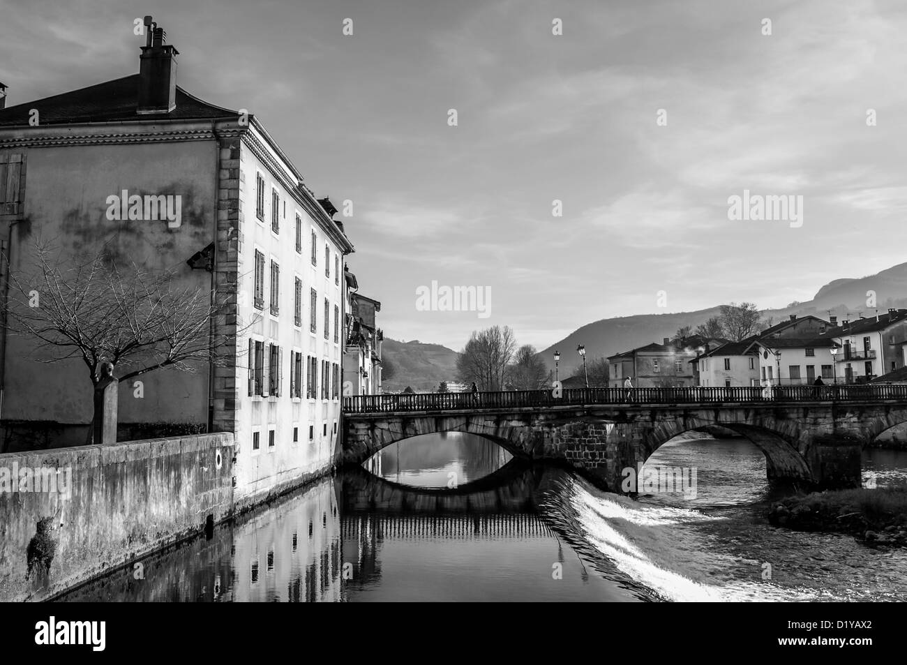 People crossing the stone bridge over the River Salat in St. Girons, Midi-Pyrenees, France. Black and white. B&W - Stock Image
