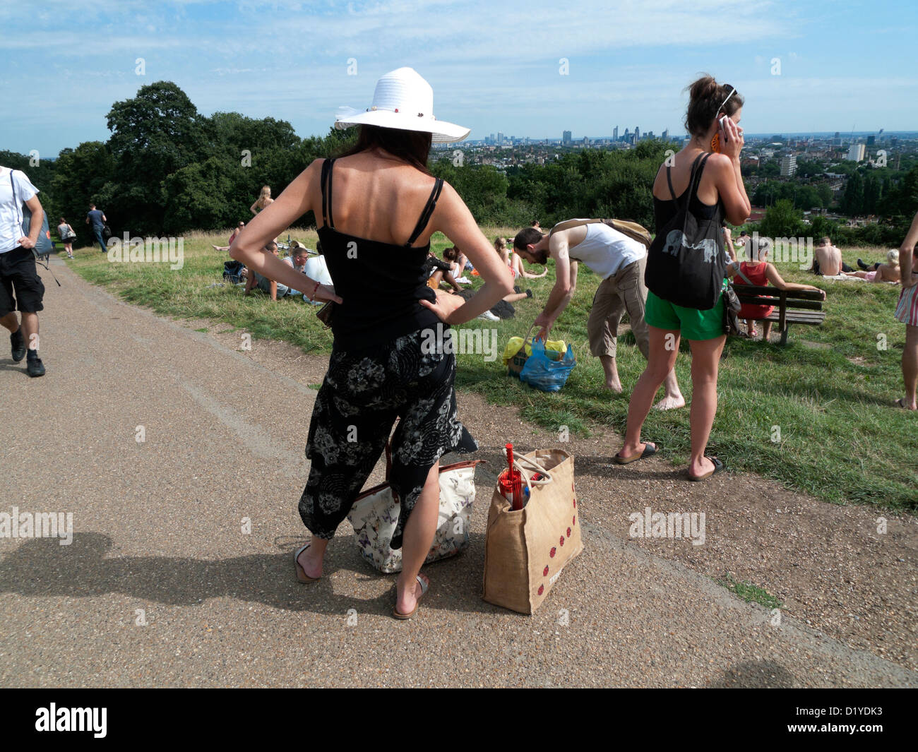 People on Parliament Hill packing up their bags after spending a hot day in August Hampstead Heath in North London - Stock Image