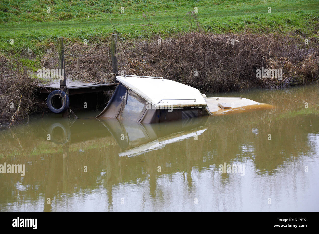 Boat sunk in flooded river - Stock Image
