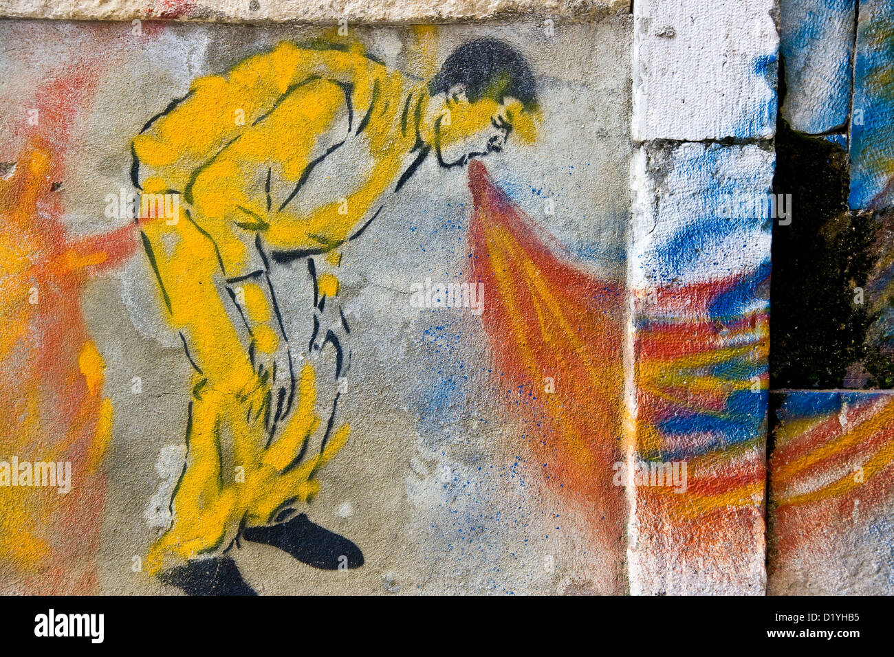 Bright colored vibrant urban graffiti street art of man vomiting on concrete wall Lisbon Portugal Europe Stock Photo