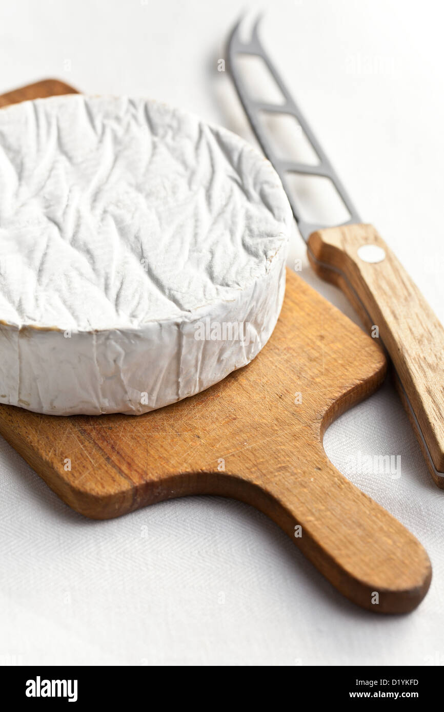 camembert cheese with knife on kitchen table - Stock Image