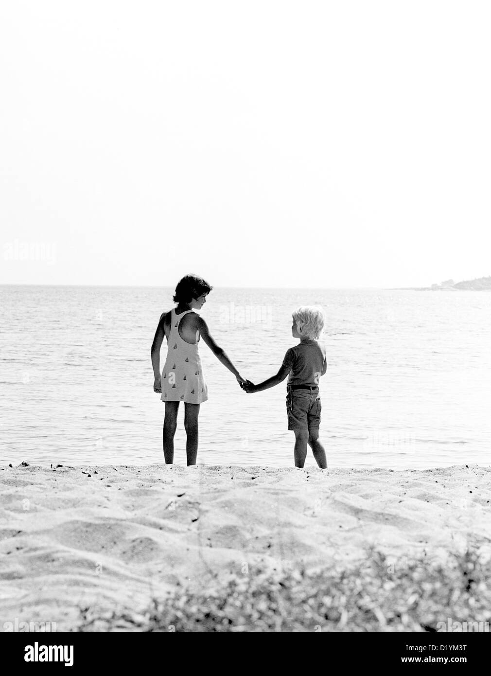 two children at the seashore looking at each other - Stock Image