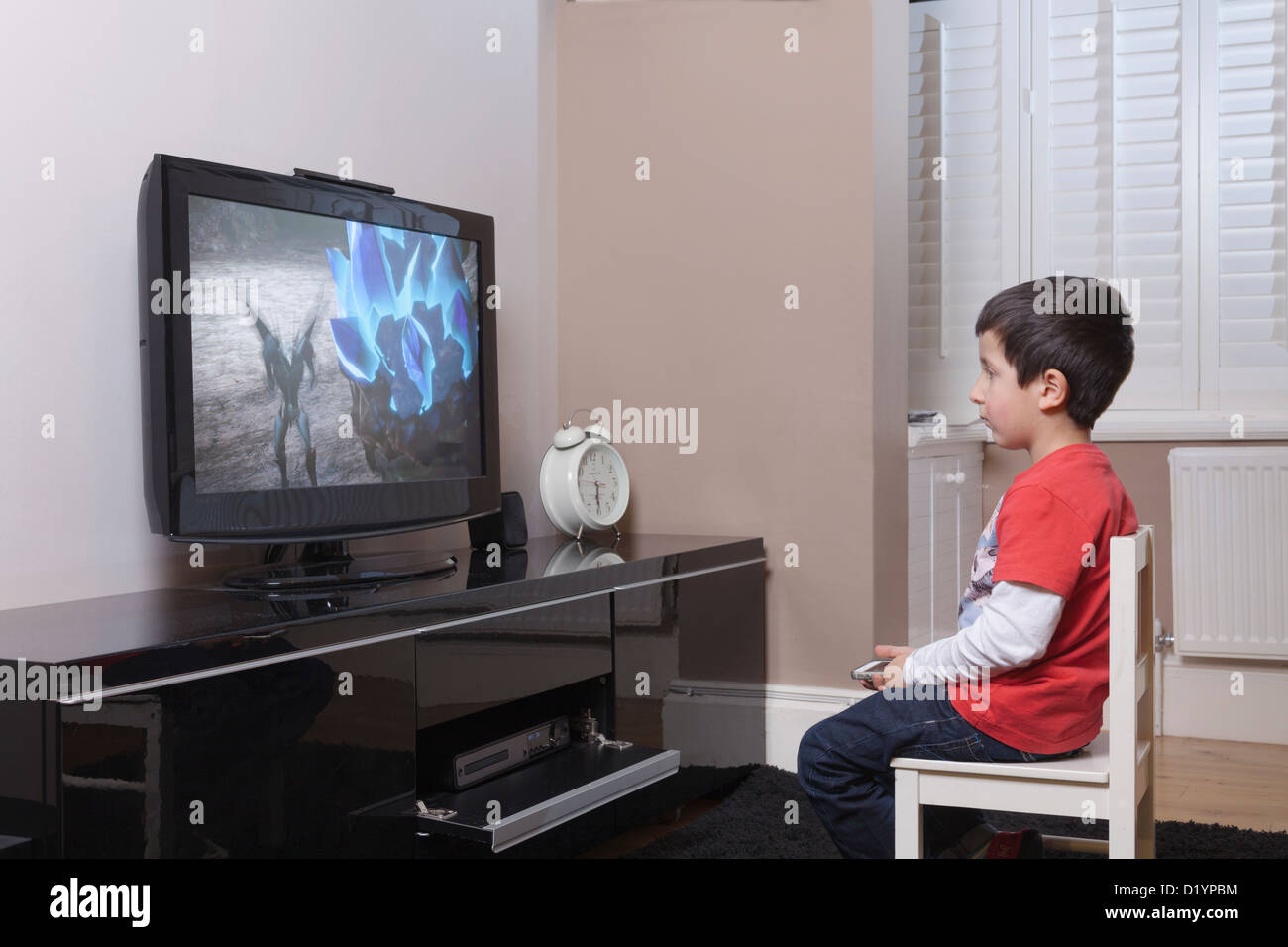 Young boy watches TV alone at home, - Stock Image