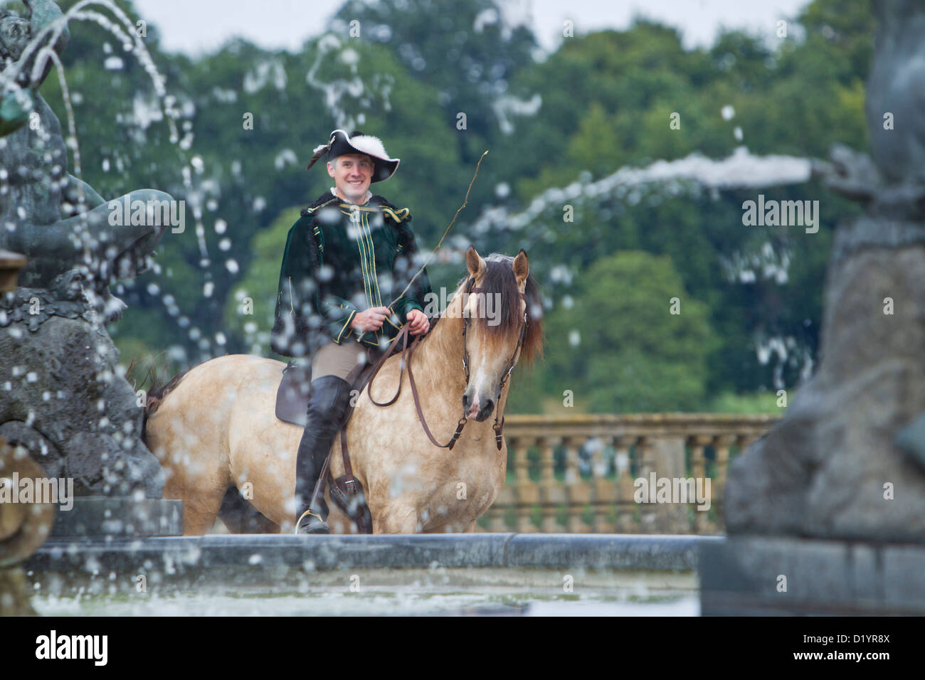 Frederiksborger with rider in historic costume standing behind a fountain in the garden of Frederiksborg PalaceStock Photo