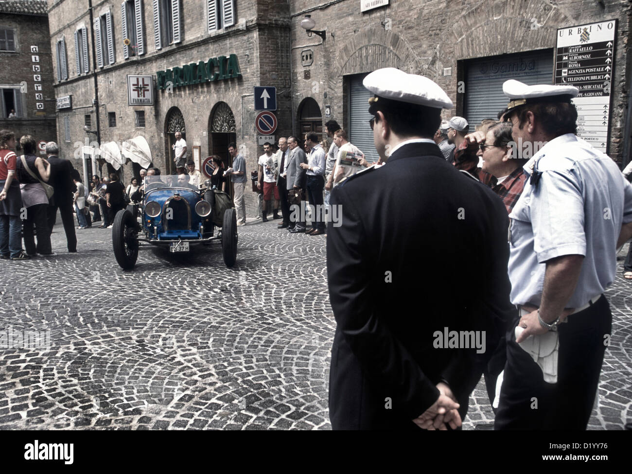 1920's Bugatti racing car watched by two Italian policemen in Urbino town centre durin the 2001 Mille Miglia - Stock Image