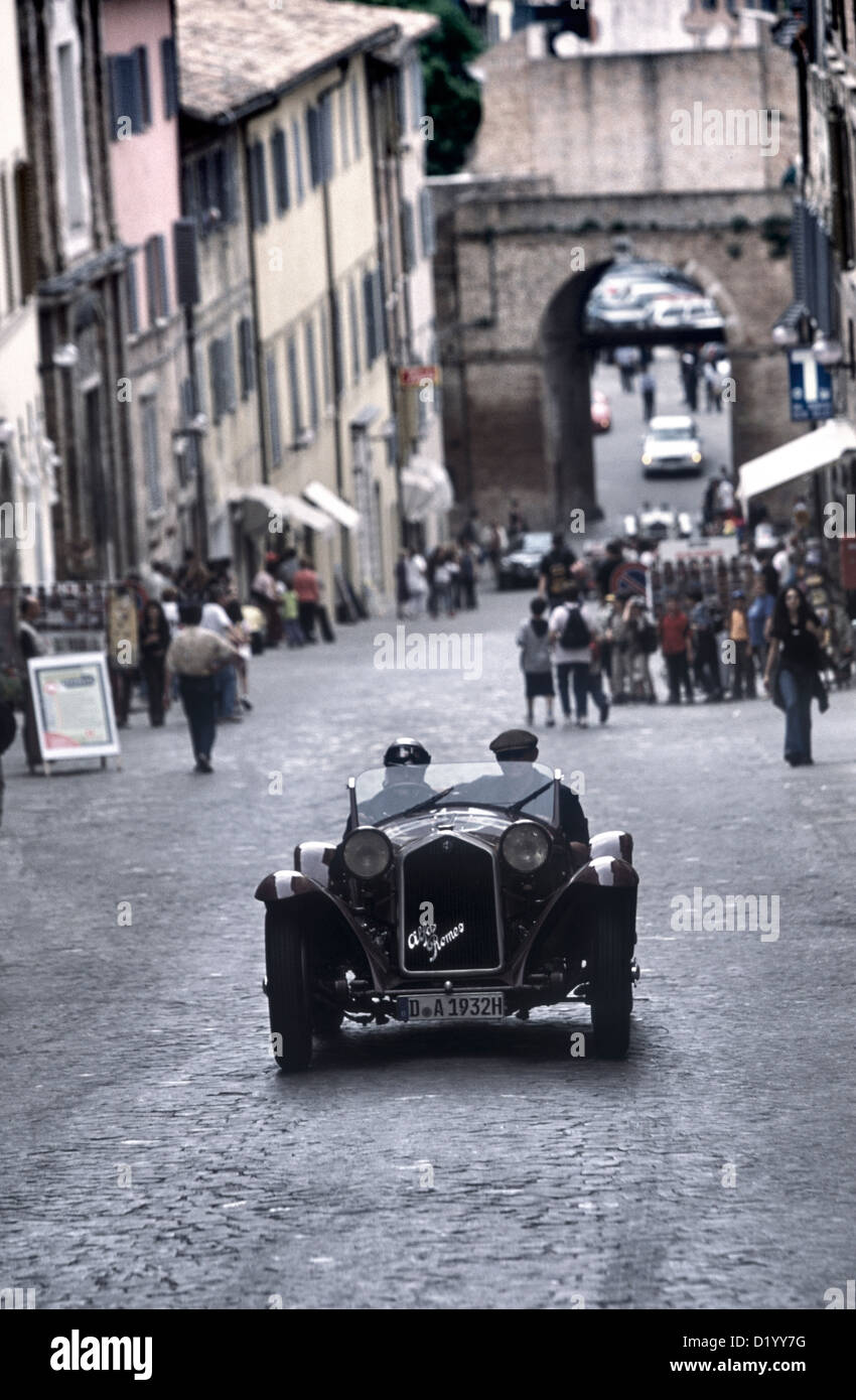 1930's Alfa Romeo sports racing car watched residents in Urbino town centre durin the 2001 Mille Miglia rally. - Stock Image