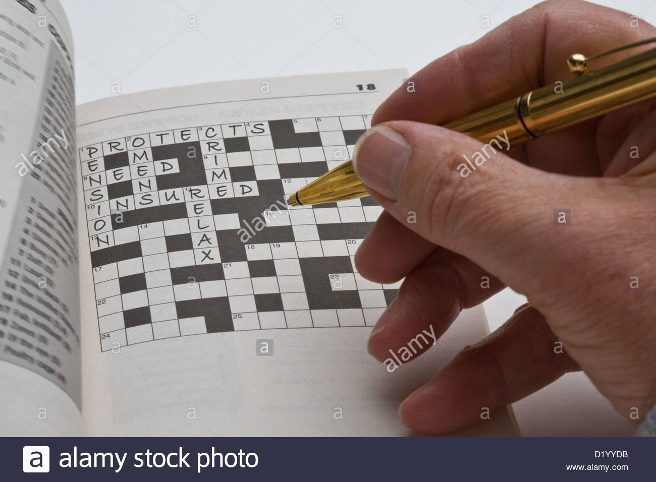 Man filling is a crossword puzzle relating to protection with insurance. - Stock Image
