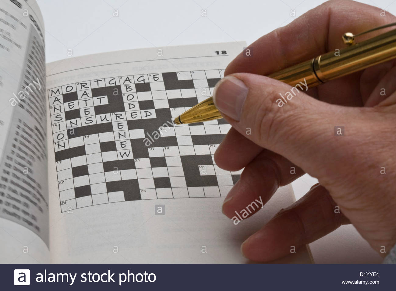 Man filling is a crossword puzzle relating to mortgages and insurance. - Stock Image
