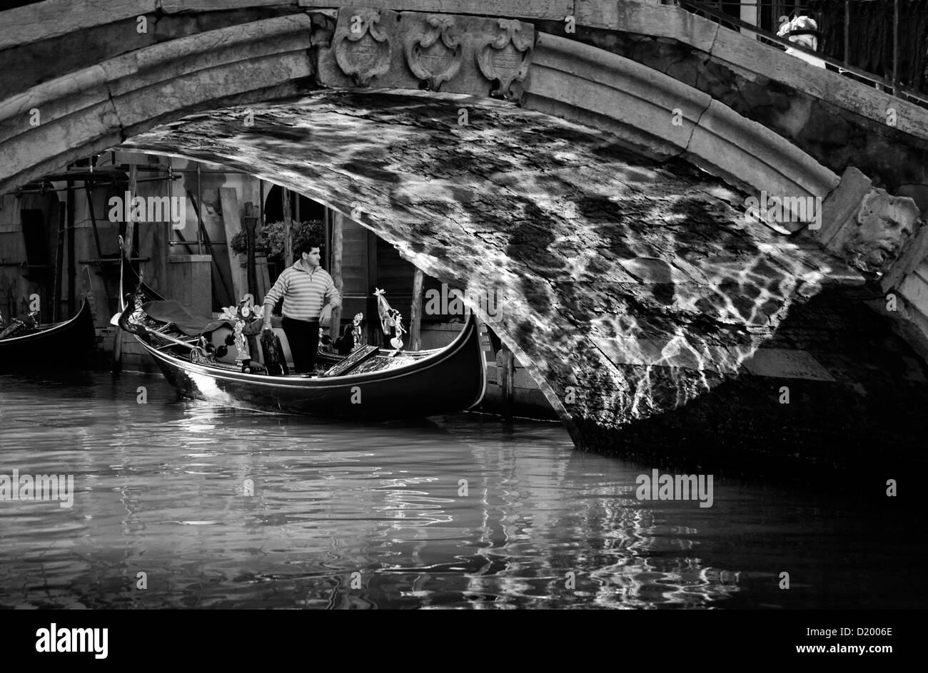 Gondola with Gondolier under the bridge, reflections of light, Venice, Italy - Stock Image
