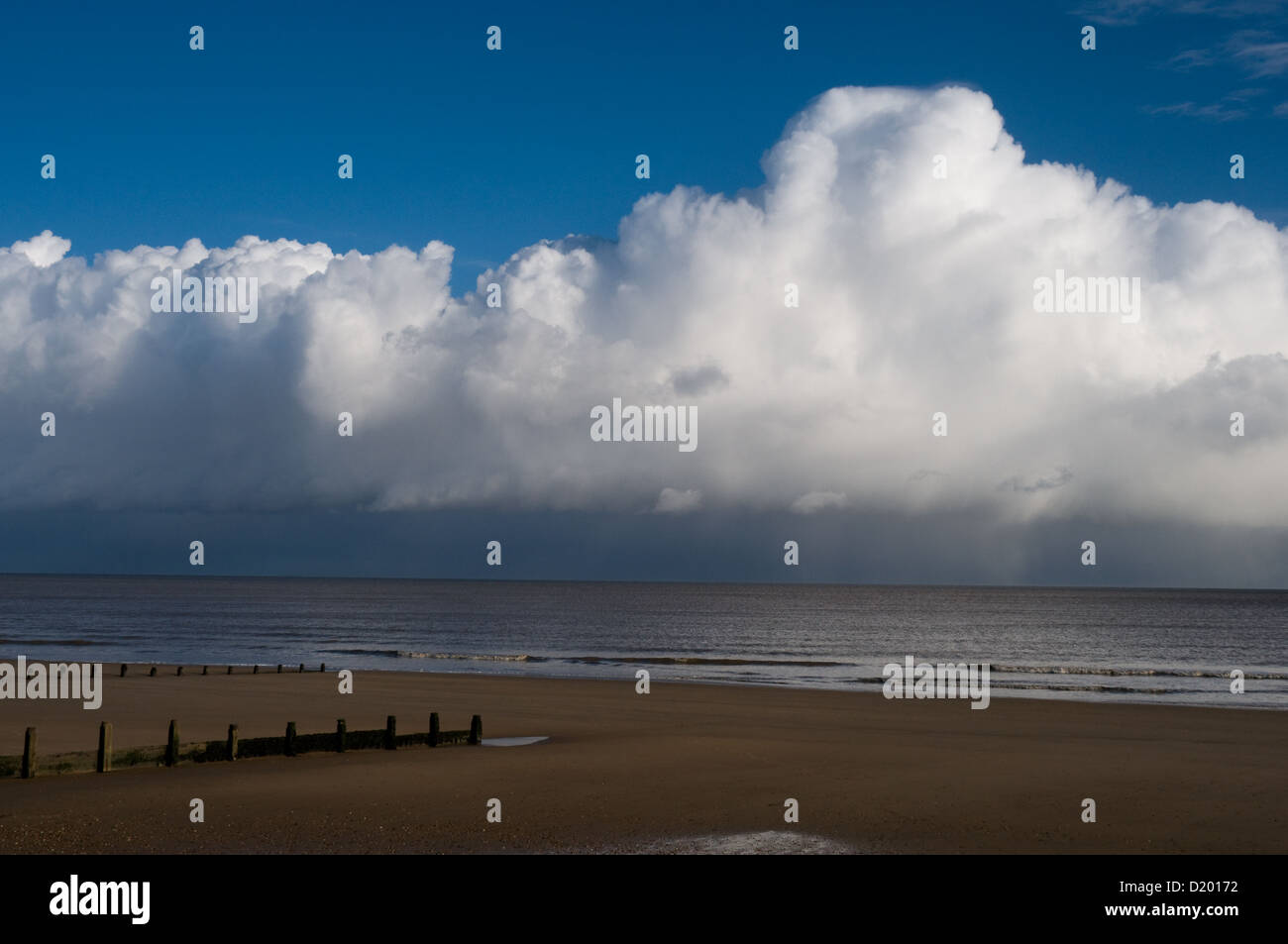 The sun shines on the sandy beach at Frinton-on-sea Essex while heavy rain clouds are a few miles out to sea Stock Photo