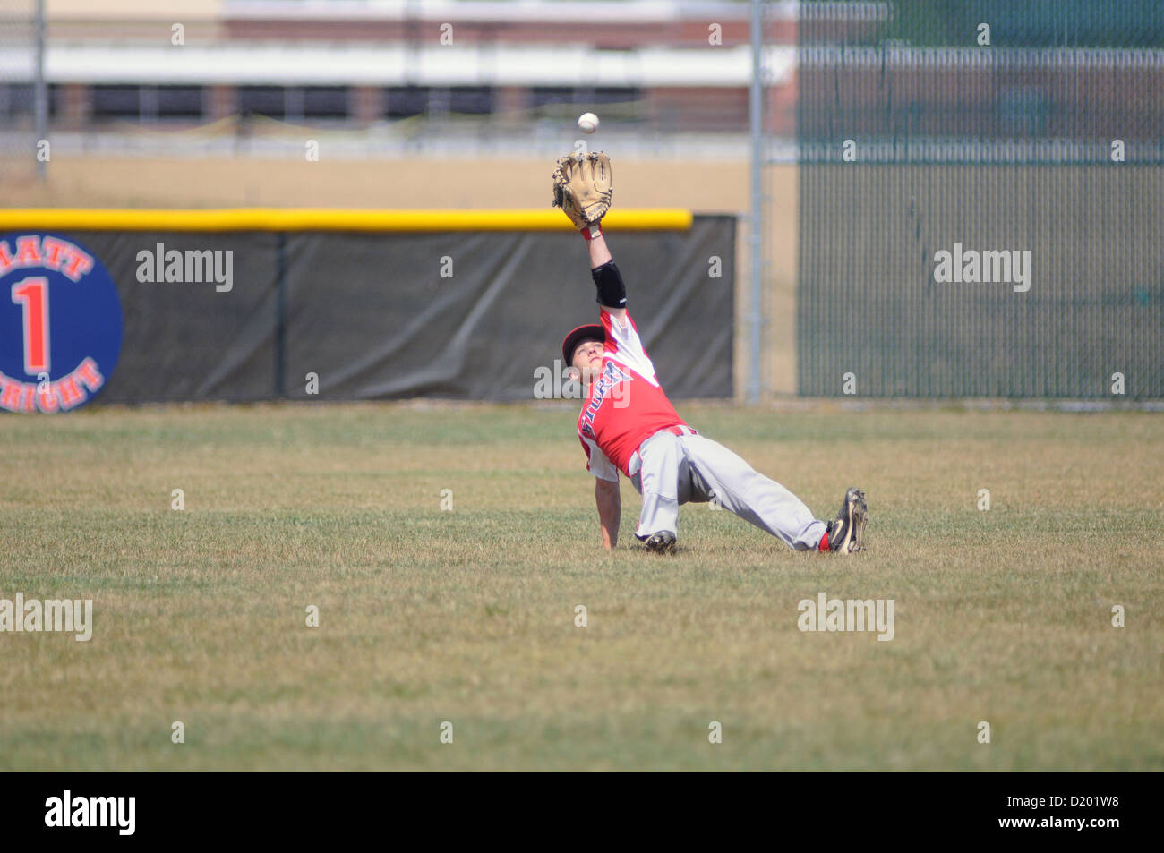 Baseball Left fielder losses his footing as a base hit bounces over the outfielder's head high school game - Stock Image