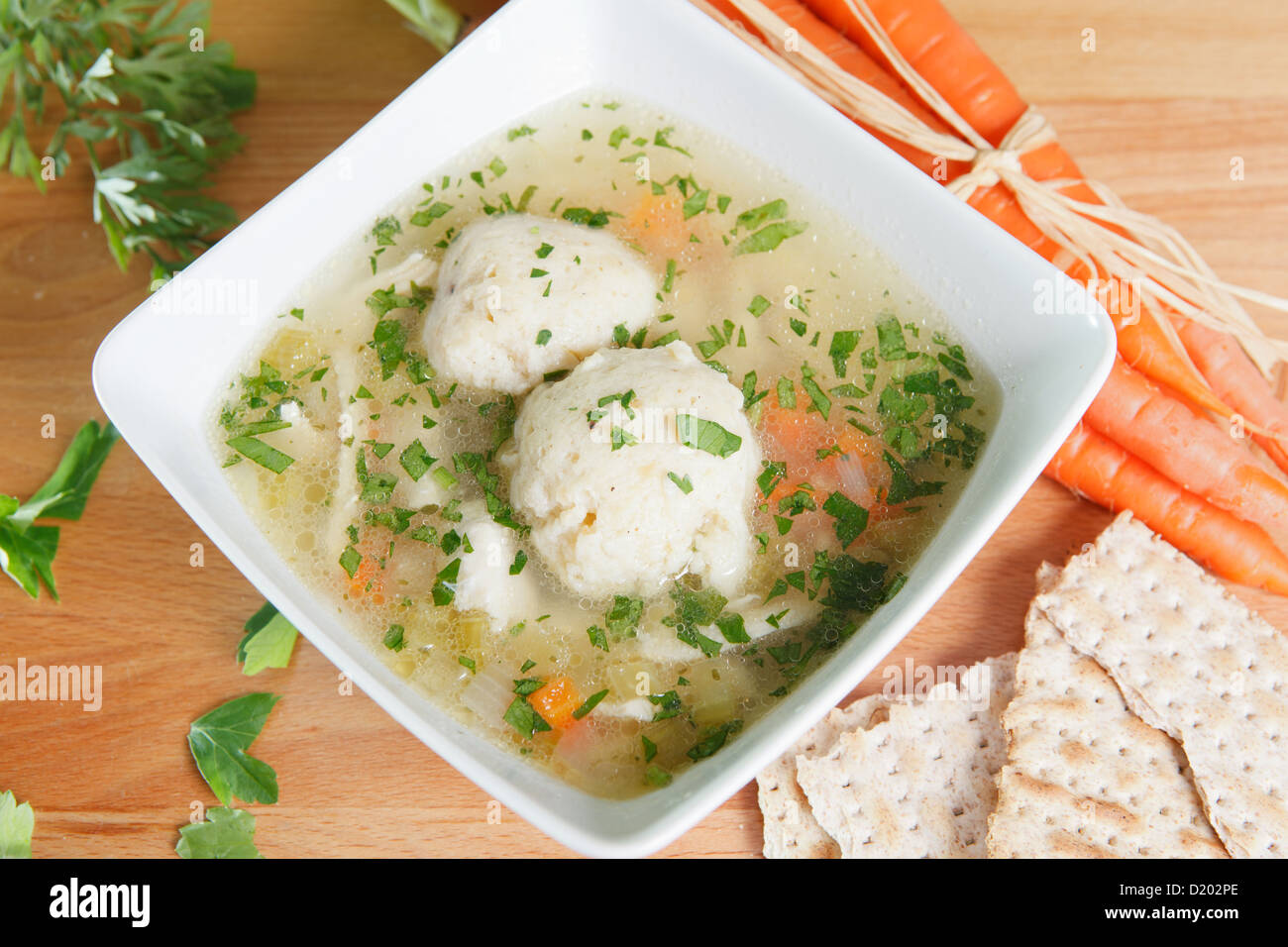 A single serving of kosher Matzah ball soup on a wooden table garnished with fresh carrots and Matzo crackers - Stock Image