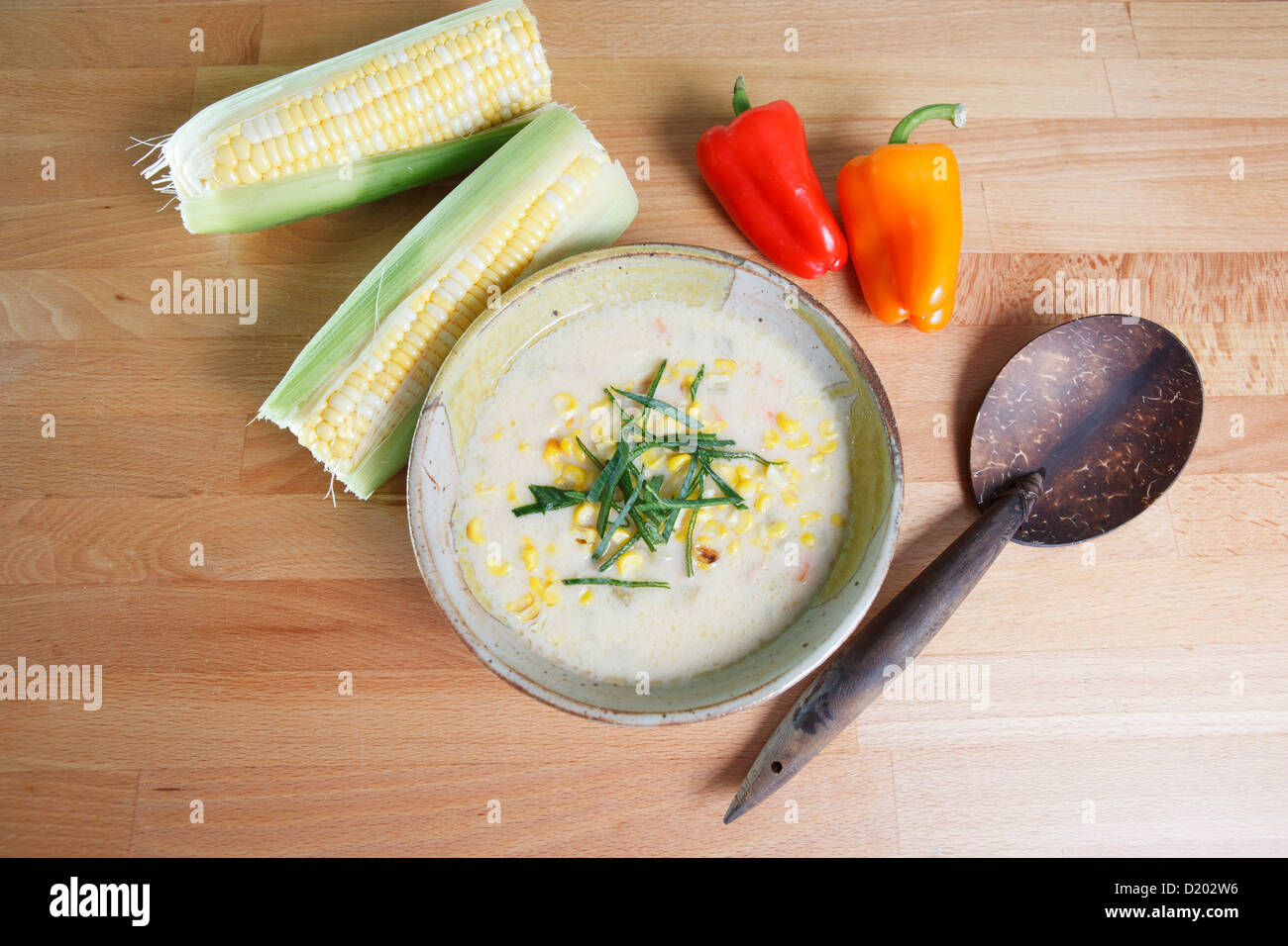 Southwestern Style Corn chowder soup garnished with whole ears of corn and colorful bell peppers - Stock Image