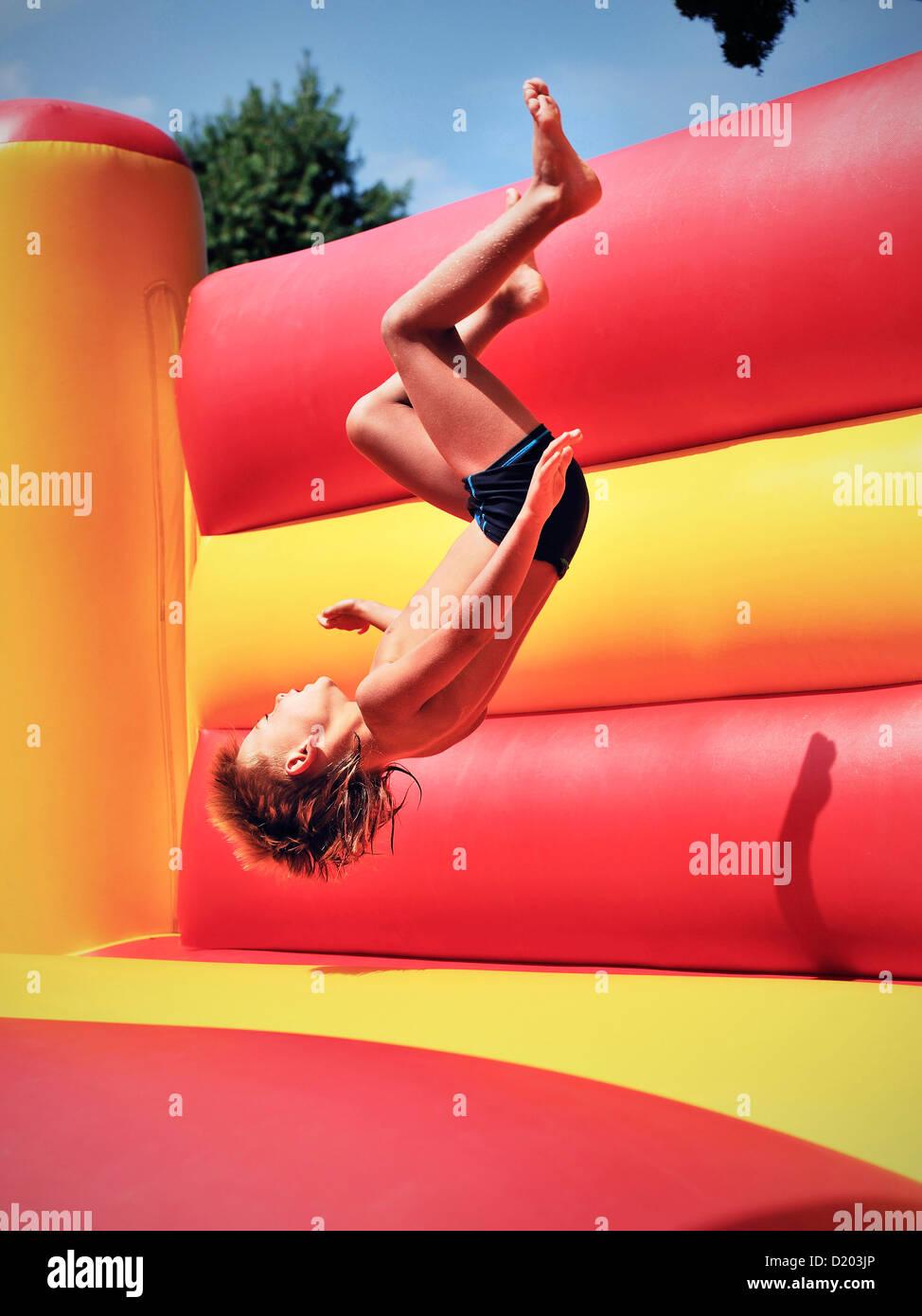 Young boy doing a somersault in a bouncy castle, Freibad Spiesel, Aalen, Schwaebische Alb, Baden-Wuerttemberg, Germany - Stock Image