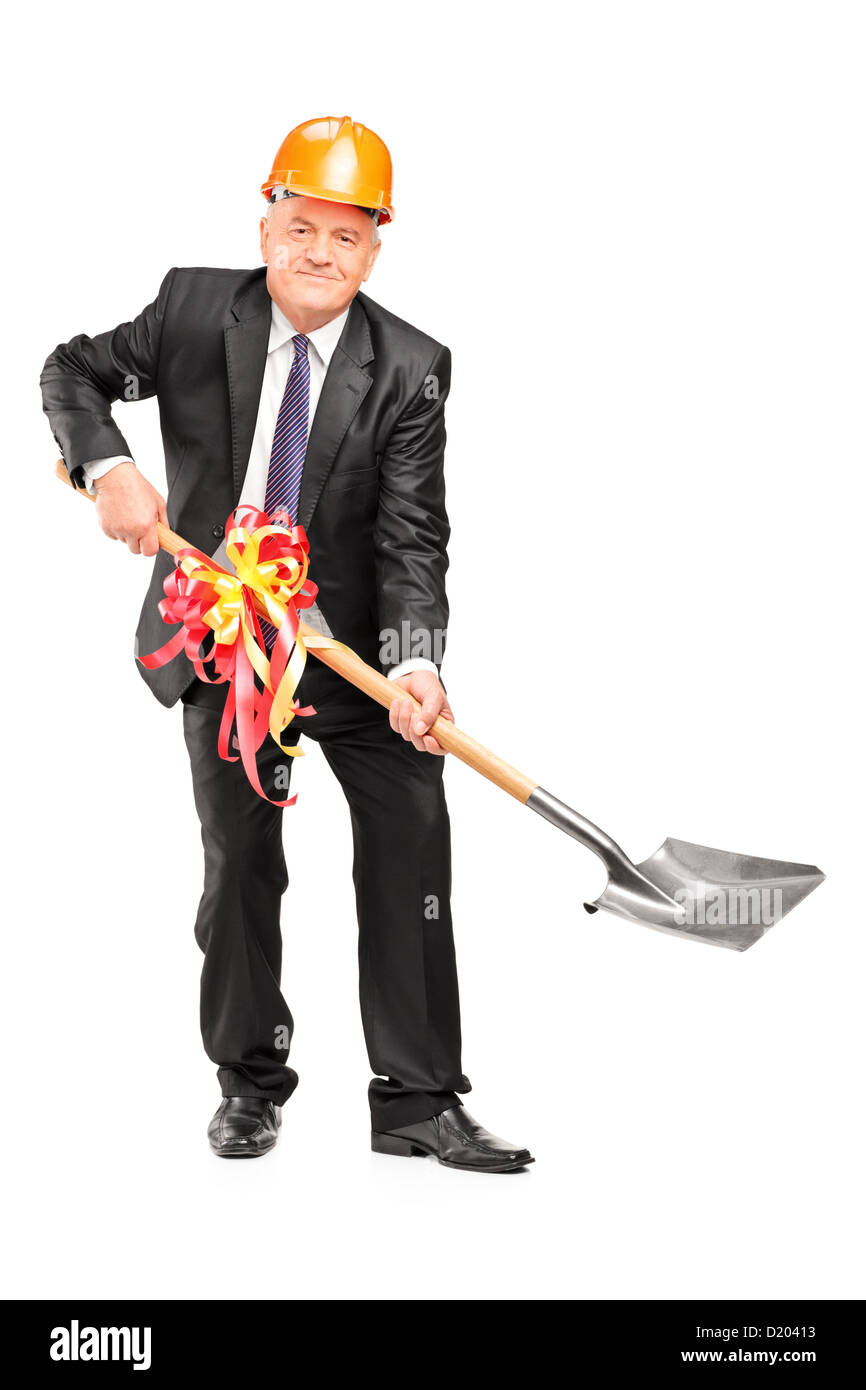 Full length portrait of a businessman wearing helmet and holding a shovel with ribbon on it isolated on white background - Stock Image