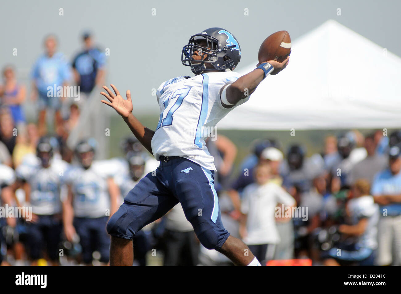 Football quarterback launching a long pass down field. USA. - Stock Image