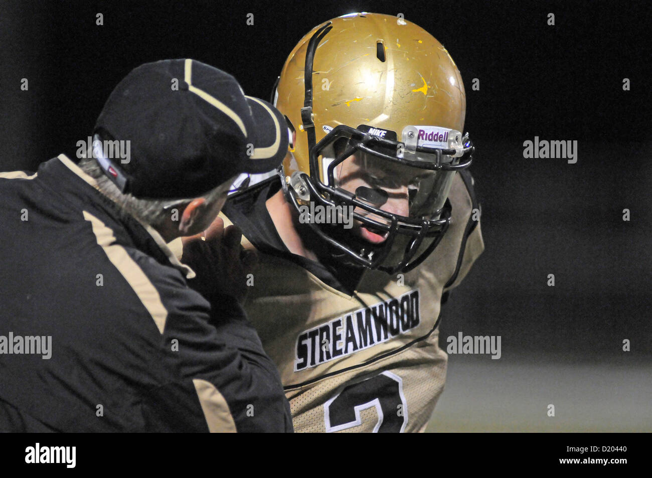 Football coach provides play instructions to his quarterback prior to a play. USA. - Stock Image