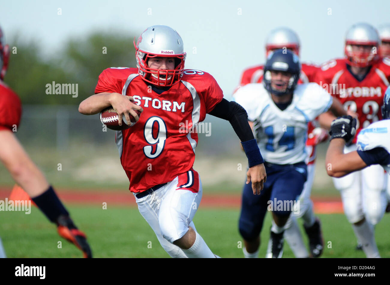 Football quarterback scrambles for yardage during a high school game. USA. - Stock Image
