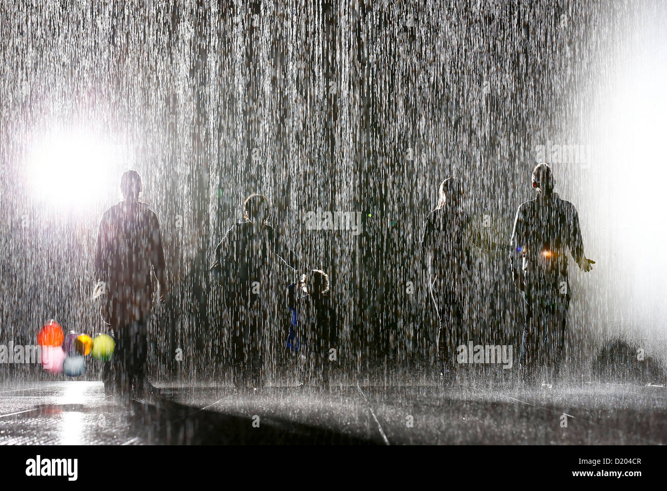 People interact with the 'Rain Room' art installation by 'Random International' at the Barbican - Stock Image